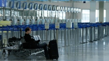 A passenger waits near empty check-in lines at Athens airport, where all flights are canceled by a 24-hour air traffic controllers' strike, part of a civil service walkout against wage freezes in Greece on Wednesday, May 5, 2010. (AP / Dimitri Messinis)
