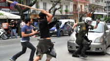 A riot policeman runs from angry protesters in the northern Greek port city of Thessaloniki, Wednesday, May 5, 2010. (AP / Giorgos Nissiotis)