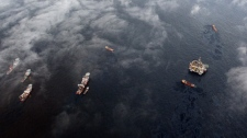 A rig drilling a relief well and support vessels are seen in the Gulf of Mexico, La., Tuesday, May 4, 2010, at the site of the recent collapse and spill of the Deepwater Horizon oil rig. (AP / Eric Gay)
