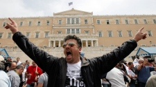 A pro-communist protester shouts slogans against the parliament in front of the parliament building in Athens, Greece on Wednesday, May 5, 2010. (AP / Dimitri Messinis)