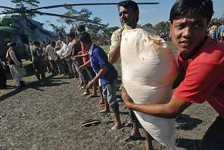 Bangladeshi villagers unload a helicopter with relief goods at Borguna, 176 kilometres south of Dhaka, Bangladesh on Sunday, Nov. 18, 2007. (AP Photo/Pavel Rahman)