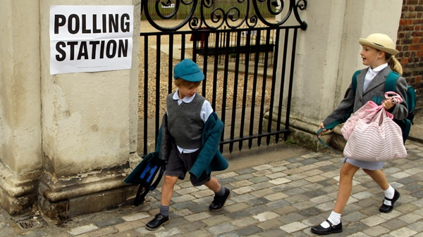 School children pass a sign outside a polling station in London, Thursday, May 6, 2010. Polls in Britain's razor-edge election opened early Thursday. (AP / Matt Dunham)