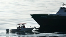 A workboat with U.S Coast Guard personnel on board intercept a pleasure craft, left, with a man and young boy aboard, after they enter restricted waters at the site of the Deepwater Horizon oil rig collapse, Thursday, May 6, 2010. The restricted zone is a 40 km radius. (AP / Gerald Herbert)