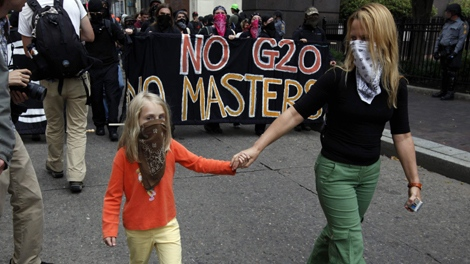 A woman walks hand in hand with her child at a protest in Pittsburgh, Friday Sept. 25, 2009. World leaders are in Pittsburgh for the G-20 summit. (AP Photo/Matt Rourke)