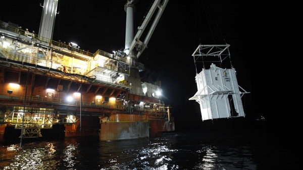 The containment vessel is lowered into the Gulf of Mexico at the site of the Deepwater Horizon rig collapse, Thursday, May 6, 2010. (AP / Gerald Herbert)