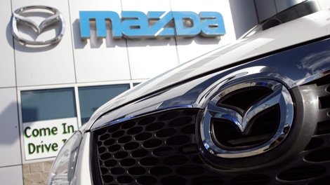 A Mazda logo glimmers on the lot of a dealership in Denver, Colo. (AP Photo/David Zalubowski)