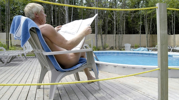 Gary Lowther, avid nudist and owner of The Oasis, a nudist camp in Cavendish, P.E.I. reads a newspaper by the swimming one recent hot summer day. (Brian McInnis / THE CANADIAN PRESS)