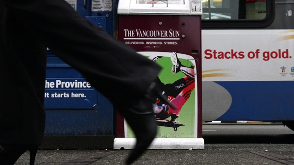A pedestrian walks past newspaper boxes of Canwest-owned Vancouver Sun and The Province daily newspapers in Vancouver, on Friday, Jan. 8, 2010. (Darryl Dyck / THE CANADIAN PRESS)
