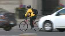 A cyclist travels beside passing cars on a busy street in Toronto.