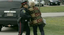 A female police officer holds a demonstrator near the OSPCA shelter in Newmarket, Ont., on Wednesday, May 12, 2010.
