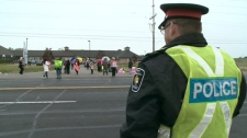 A York Regional Police officer stands watch as protestors make their voices heard outside the clinic in Newmarket, Ont., Thursday, May 13, 2010.