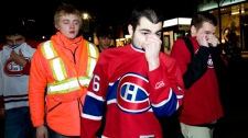 Montreal Canadiens' fans cover their faces after police fired tear gas as fans celebrated the team's win over the Pittsburgh Penguins in the NHL Eastern Conference semi-final hockey series in downtown Montreal Wednesday, May 12, 2010.( Graham Hughes / THE CANADIAN PRESS)