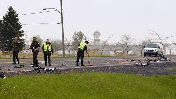 Police examine the scene where a pickup truck plowed into a group of cyclists leaving one dead and five injured in Rougemont, Quebec, Friday, May 14, 2010. (Ryan Remiorz / THE CANADIAN PRESS)