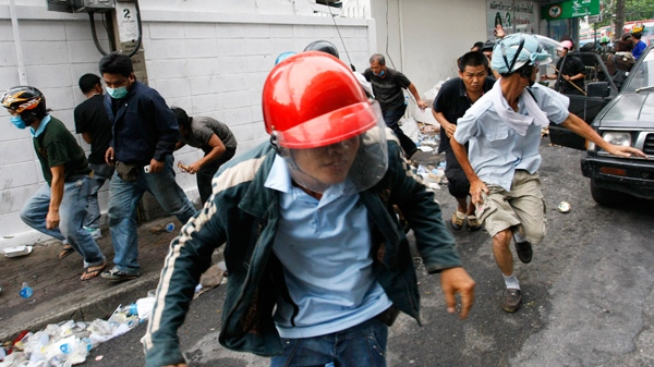 Anti government protesters run away after Thai soldier shot their weapons in Bangkok Thailand on Sunday, May 16, 2010. (AP / Wason Wanichakorn)