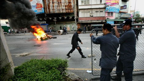 Thai police officers remove a fire road block at the edge of Victory Monument intersection, Monday, May 17, 2010 in Bangkok, Thailand. (AP / Wally Santana)
