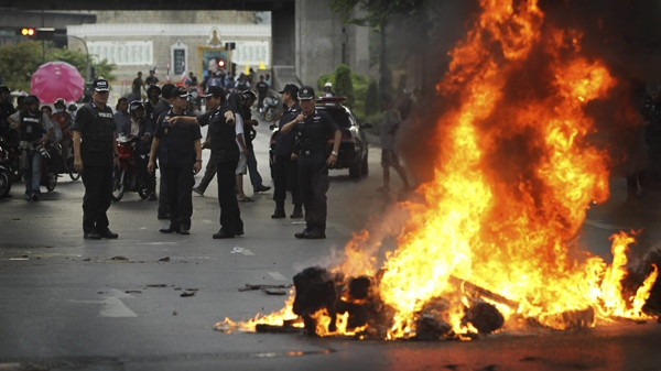 Thai police officers arrive at the edge of Victory Monument intersection to disperse protesters and remove a fire road block, Monday, May 17, 2010 in Bangkok. (AP / Wally Santana)
