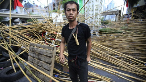 "A ""Red Shirt"" activist stands guard at their barricade as they expect a crackdown on Monday, May 17, 2010 in Bangkok, Thailand. (AP Photo/Wong Maye-E)"