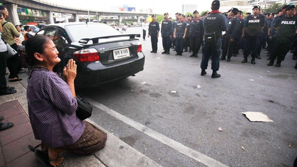 A Thai woman prays as Thai policemen get ready soon after 3 p.m. deadline at Victory Monument in Bangkok, Thailand, Monday, May 17, 2010. (AP / Manish Swarup)
