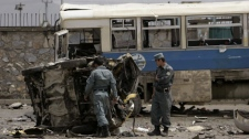 Afghan policemen look at the mangled remains of a vehicle after a suicide attack in Kabul, Afghanistan, Tuesday May 18, 2010. (AP Photo/Ahmad Massoud)