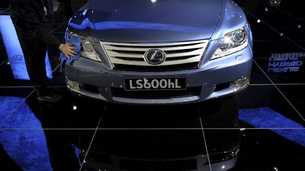 A cleaner wipes a Lexus LS 600hL on display at the booth of Toyota Motor Corp. during the China Auto Show in Beijing, Friday, April 23, 2010. (AP Photo / Andy Wong)