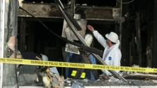 Investigators sift through damage caused by a firebomb at an Ottawa downtown bank Wednesday, May 19, 2010. (Fred Chartrand / THE CANADIAN PRESS)