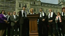 Parti Quebecois leader Pauline Marois (centre), surrounded by members of opposition parties, speaks in front of the National Assembly on Wednesday, May 19, 2010.