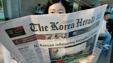 A South Korean woman reads a newspaper reporting on the results of an investigation into the sinking of a South Korean naval ship at a news stand in Seoul, South Korea, Thursday, May 20, 2010. (AP / Ahn young-joon)