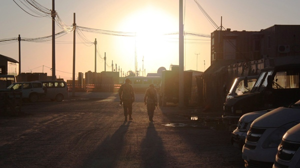 Two Canadian soldiers walk into the Christmas Day sunset at Kandahar Airfield in Afghanistan on Friday, Dec. 25, 2009. (Colin Perkel / THE CANADIAN PRESS)