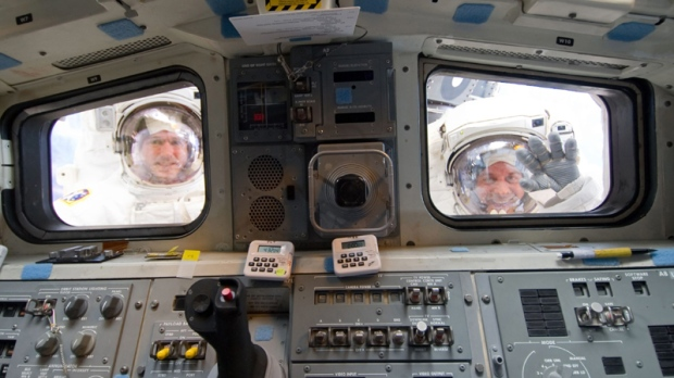 NASA astronauts Michael Good (left) and Garrett Reisman, both STS-132 mission specialists, look through the aft flight deck windows of space shuttle Atlantis in this image provided by NASA during the mission's third and final session of extravehicular activity Friday May 21, 2010 as construction and maintenance continue on the International Space Station. (AP Photo/NASA)