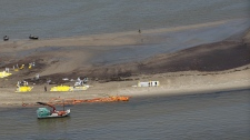 Workers are seen involved in cleanup efforts of the Deepwater Horizon oil spill, with oily water around them near the South Pass of the Mississippi River along the Lousiana coast near Venice La., Thursday, May 27, 2010. (AP / Gerald Herbert)