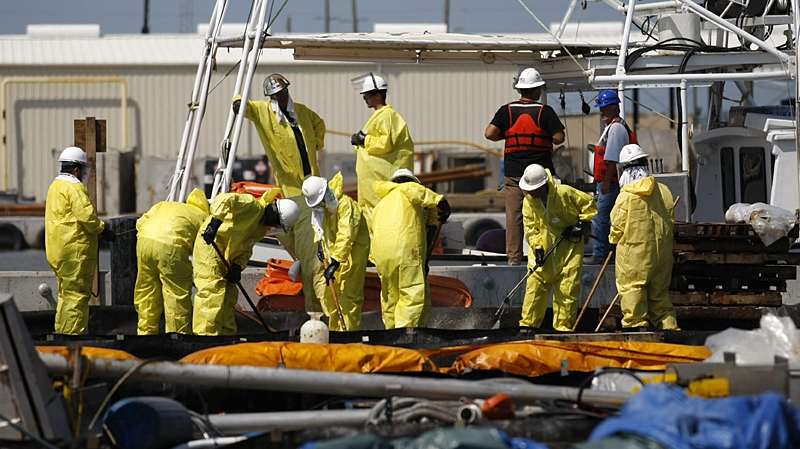 Workers clean a boom to be deployed in the response to the Deepwater Horizon oil spill at a U.S. Coast Guard command center in Venice, La., Thursday, May 27, 2010. (AP / Gerald Herbert)