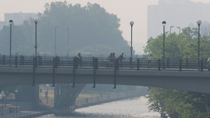 Commuters make their way over the Rideau Canal as a thick layer of smoke from forest firest in Quebec covers the Ottawa area on Monday, May 31, 2010. (Sean Kilpatrick / THE CANADIAN PRESS)