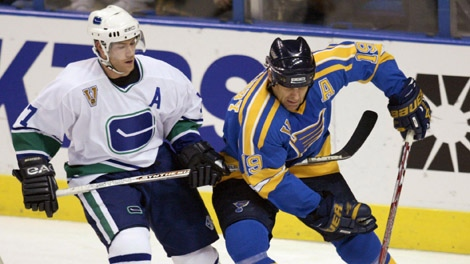 Vancouver Canucks Brendan Morrison tries to slow down St. Louis Blues Scott Mellanby as he skates around the goal with the puck in the second period Thursday, Jan. 29, 2004 in St. Louis.(AP PHOTO/Tom Gannam)