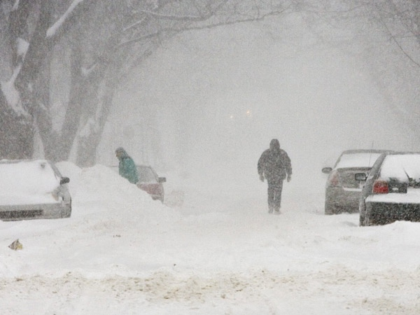 A pedestrian walks on a snow covered street Monday Dec. 3, 2007 in Quebec City. (Jacques Boissinot / THE CANADIAN PRESS)