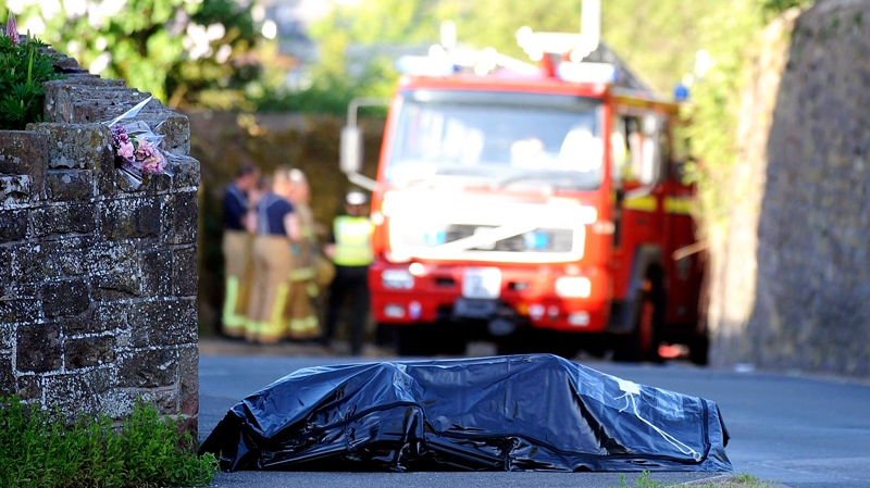The body of a victim covered by a sheet lies in the street, after a man went on a shooting spree throughout the Lake District, in Egremont, northwestern England, Wednesday, June 2, 2010. (AP / Scott Heppell)