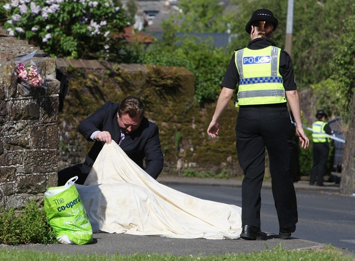 Police look under a sheet covering a body on Hagget End Road, in Egremont northwest England where a person was shot dead when taxi driver Derrick Bird went on a shooting rampage in northwest England Wednesday June 2, 2010. (AP / Andrew Milligan)