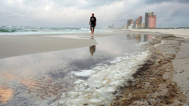 A man walks past oil residue on the beach in Gulf Shores, Ala. Saturday, June 5, 2010. (AP / Dave Martin)