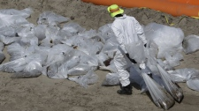 A worker removes oil that has washed ashore from the Deepwater Horizon spill, Sunday, June 6, 2010 in Grand Isle, La.. (AP Photo/Eric Gay)