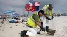 Oil cleanup workers hired by BP pick up tar balls as they work along Pensacola Beach, Fla., Sunday, June 6, 2010. Oil from the Deepwater Horizon disaster has started washing ashore on the Alabama and Florida coast beaches. (AP Photo/Dave Martin)
