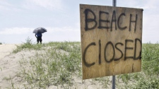 A security guard keeps watch as workers remove oil that has washed ashore from the Deepwater Horizon spill, Sunday, June 6, 2010 in Grand Isle, La.. (AP Photo/Eric Gay)