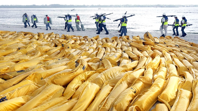 """Workers carry """"pom poms"""" to soak up oil at the Pensacola inlet Sunday, June 6, 2010, in Pensacola Beach, Fla. (AP / Orlando Sentinel, George Skene)"""