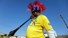 A man blows his vuvuzela on the street before the opening game of the soccer World Cup between South Africa and Mexico in Atteridgeville near Pretoria, South Africa, Friday, June 11, 2010. (AP Photo/Gero Breloer)