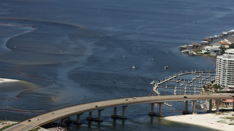 Oil sheen is seen still streaking under the Perdido Pass Bridge from the spill in the Gulf of Mexico off the Alabama coast as viewed from a Coast Guard HC-144A plane Thursday, June 10, 2010 in Perdido, Ala. (Mobile Press-Register / John David Mercer)