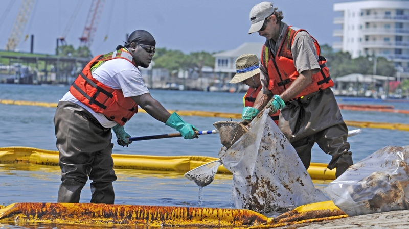 Workers wearing hip-boots use nets to scoop up floating tar that has seeped into the inland waterways at Perdido Pass, Thursday, June 10, 2010, at Boggy Point boat ramp, Orange Beach, Ala. (The Miami Herald / Marice Cohn Band)