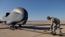 U.S. Airman 1st Class Max Todd hooks up the RQ-4B Global Hawk to a tow bar