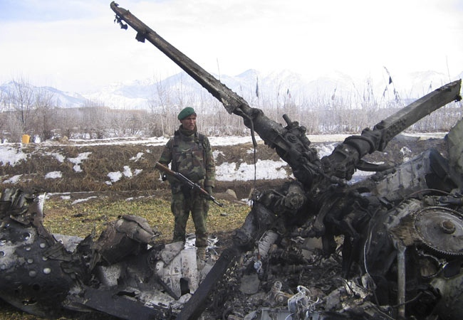 An Afghan soldier stands guard near the wreckage of an Afghan army helicopter which crashed in the Salar district, southwest of Kabul, Afghanistan on Monday, Dec. 10, 2007. (AP / Rahmatullah Naikzad)