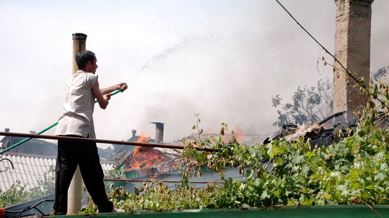 An ethnic Uzbek tries to extinguish a fire with water from a garden hose at a burning residence, which was allegedly torched by Kyrgyz men, in Jalal-Abad, Kyrgyzstan, Sunday, June 13, 2010. (AP / Zarip Toroyev)