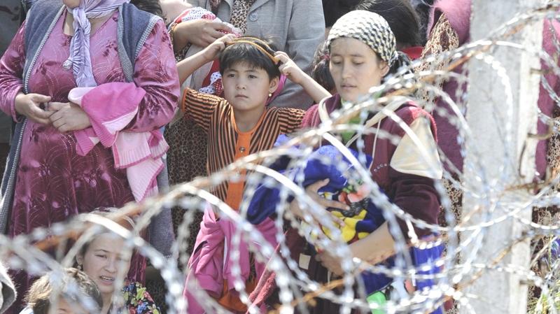 Ethnic Uzbek refugees fleeing ethnic violence in Kyrgyzstan stand in line in no-man's-land near the Uzbek village of Jalal-Kuduk waiting for permission to cross into Uzbekistan, Monday, June 14, 2010. (AP / Anvar Ilyasov)