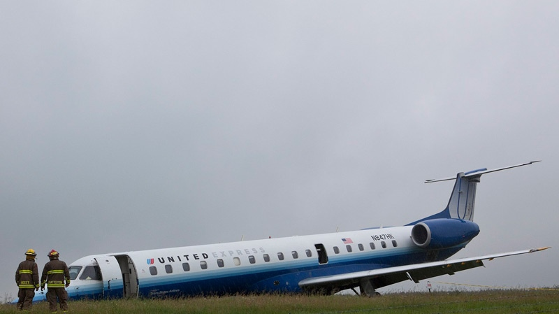 Ottawa firefighters take a closer look at a United Airlines Express airplane which slid off of the runway at Ottawa International Airport in Ottawa on Wednesday, June 16, 2010. (Pawel Dwulit / THE CANADIAN PRESS)