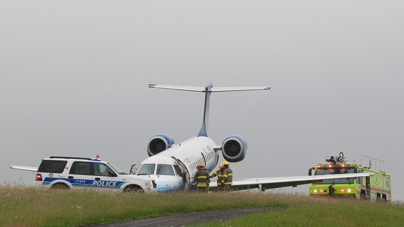 Ottawa firefighters and police gather around a United Airlines Express airplane which slid off of the runway at Ottawa International Airport in Ottawa on Wednesday, June 16, 2010. (Pawel Dwulit / THE CANADIAN PRESS)
